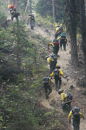 Ten firefighters with gear hike up trail
