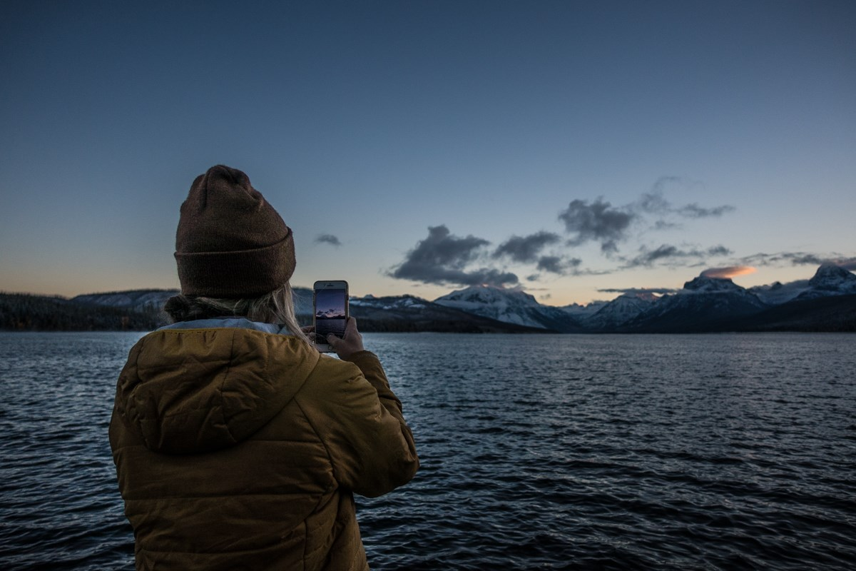 A person in a coat and hat photographs sunrise over mountains with a lake in the foreground.