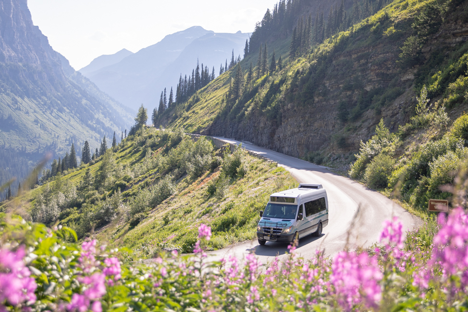 A shuttle bus drives on a mountain road.