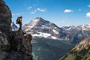 Backpacker stands on cliff edge looking upon mountain vista