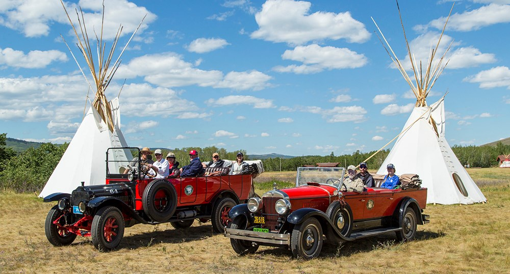 roofless historic red touring cars with seated passengers in front of tipis