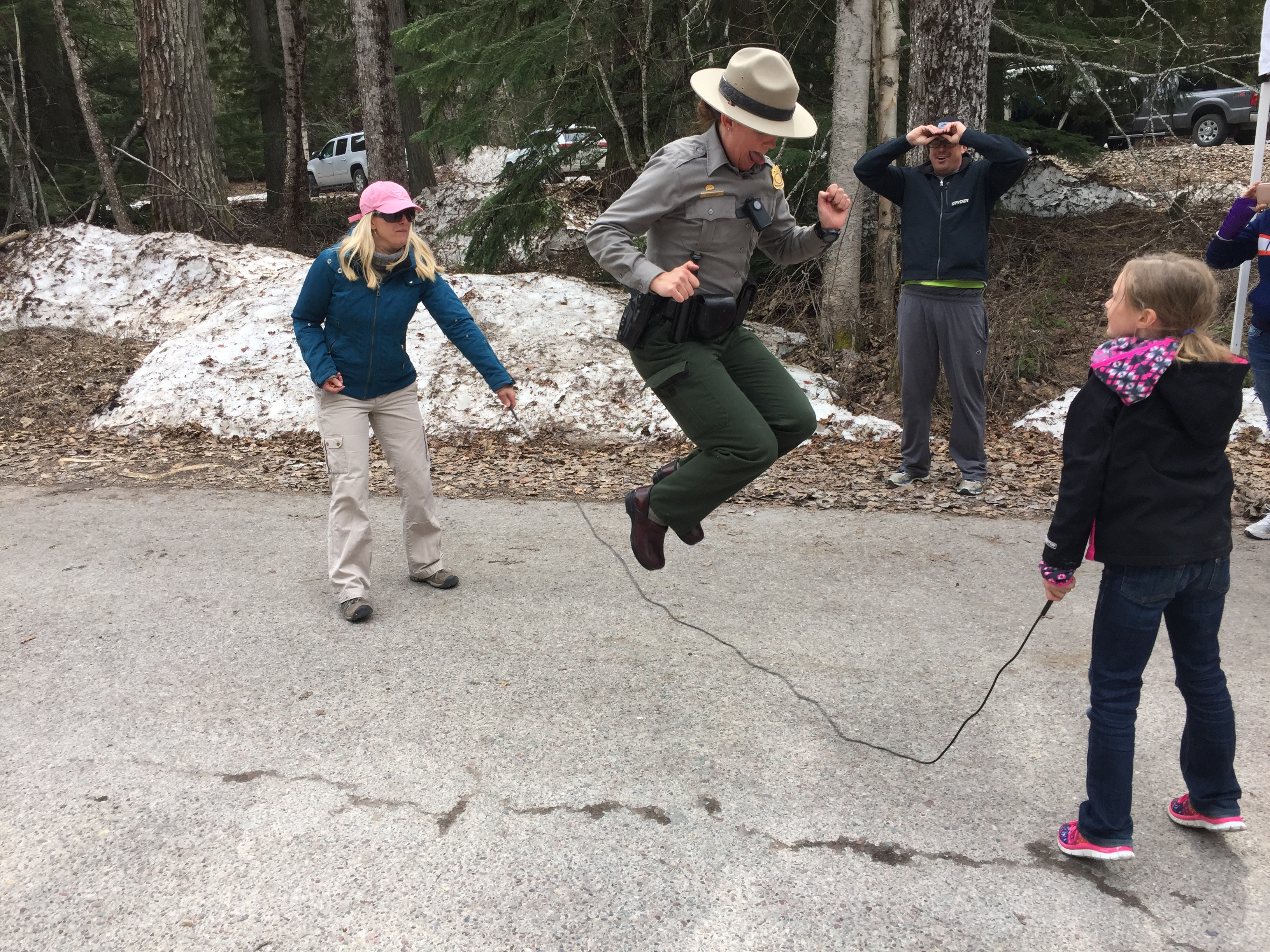 A park ranger wearing a flat hat jumps rope with two visitors.