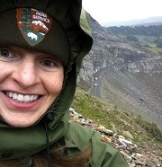 Selfie of smiling ranger with mountain road far below