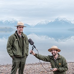 Two National Park Service rangers stand on a lake show in uniform and one of them holds a microphone up to the other one.