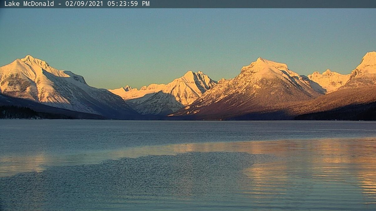 view of lake mcdonald just before sunset with pink mountains