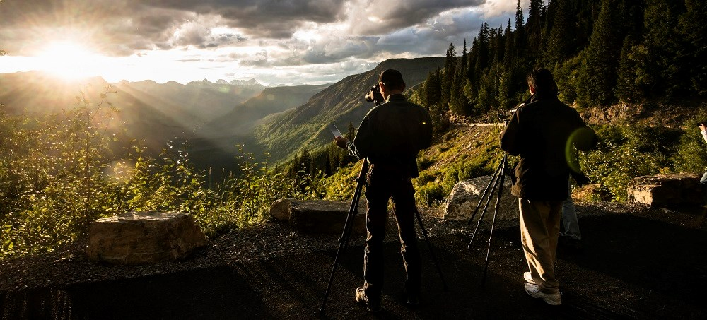 two photographers with tripods face a sunset over mountains