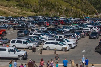 A very full parking lot in the mountains with crowds of people around.