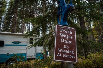 "A water faucet with a sign that says, ""Fresh Water Only No washing At Faucet."" A camper in the forest in the background."