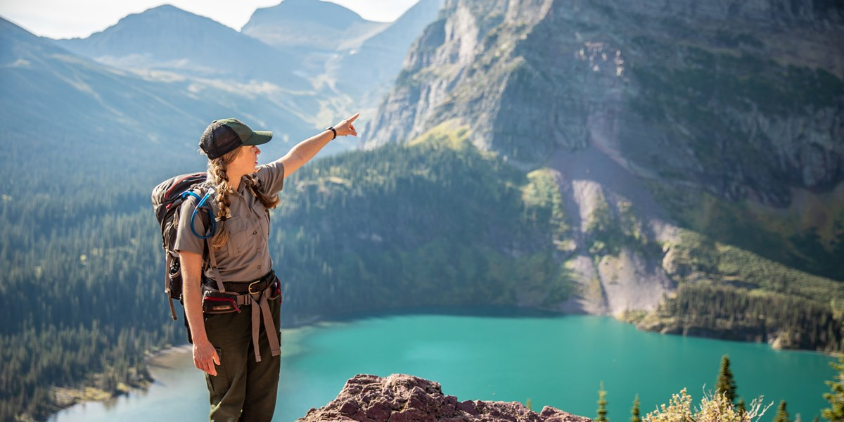 A ranger points with a lake and mountains in the background.