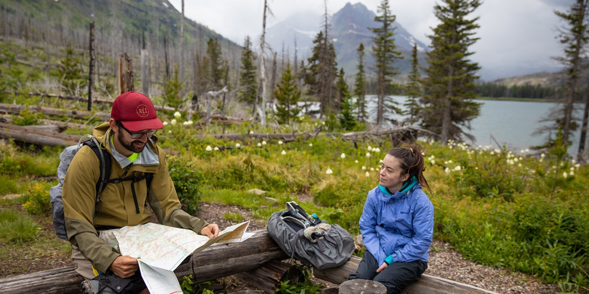 Two people look at a map in the backcountry.