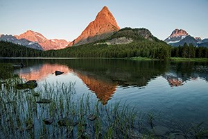 warm glow on mountain top reflected in cool lake surrounded by vegetation