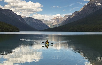 Solitary kayaker on mountain lake takes a pause from paddling
