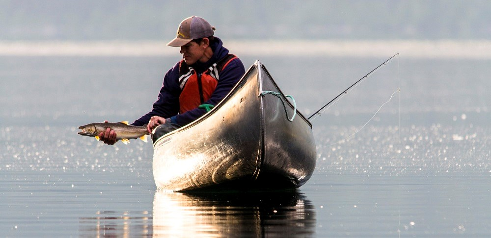 man in canoe about to release speckled fish into water