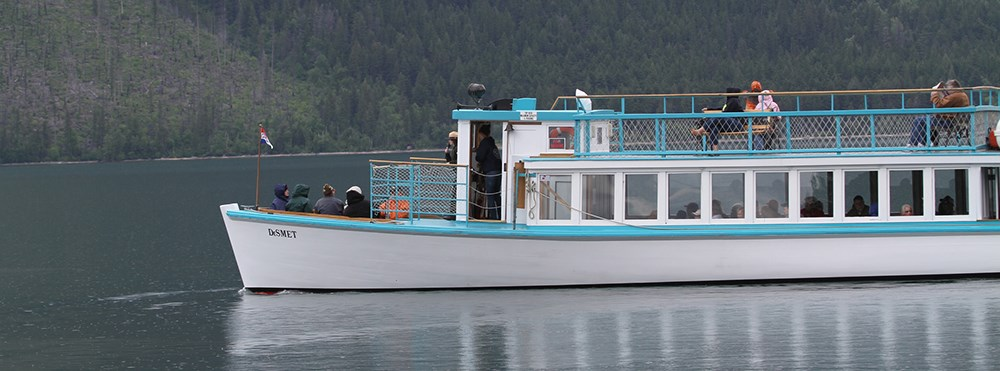 large wooden boat cruises lake with visitors on top deck, bow, and in cabin