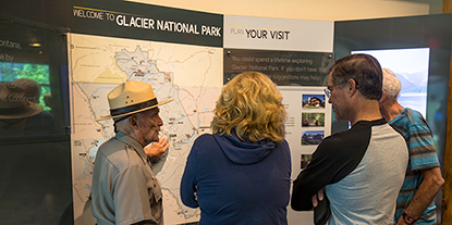 Ranger assisting visitors at a park map exhibit