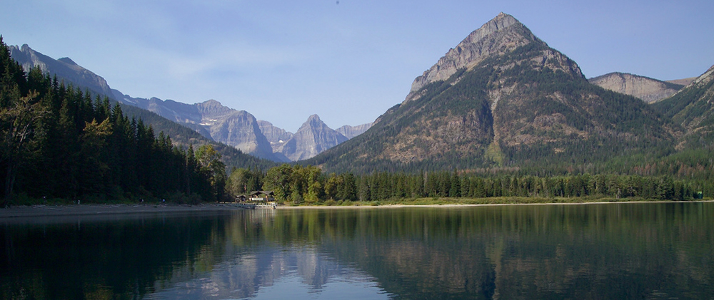 ranger station on lakeshore surrounded by peaks