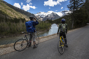 Cyclists pause along road and look at mountain vista through binoculars