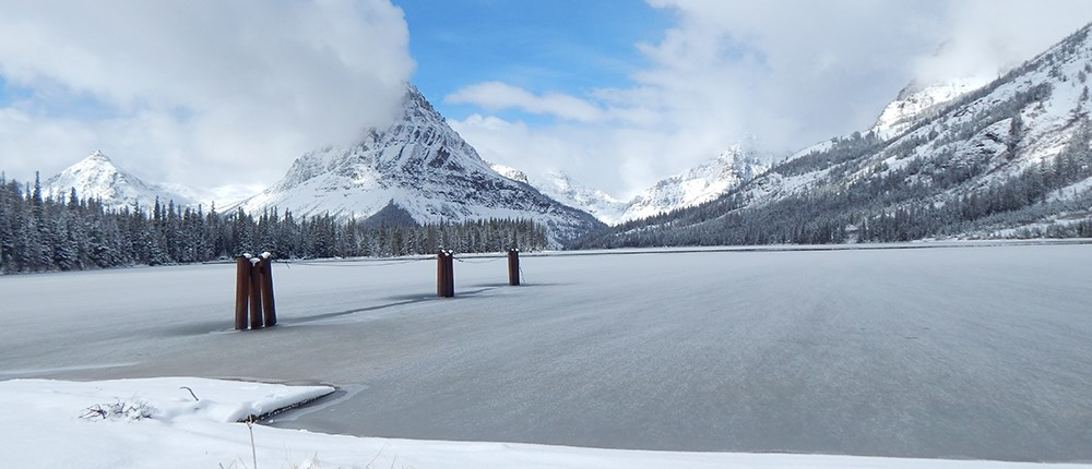 frozen mountain lake with dock pylons sticking out of ice