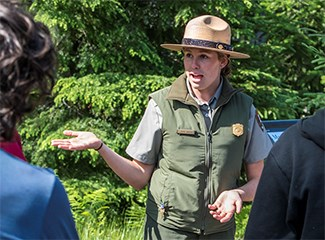 Ranger in summer flat hat speaks to group