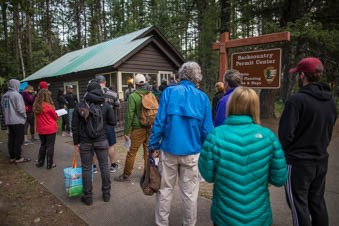A crowd of people stand in line outside the backcountry permit office at 7:00AM.