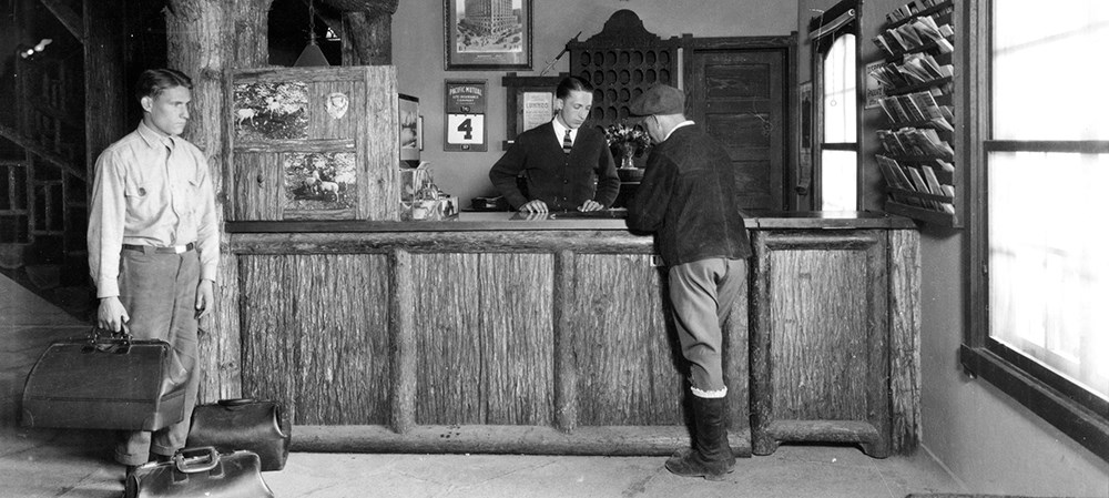 historic image of man at lodge reservation desk with employee holding luggage