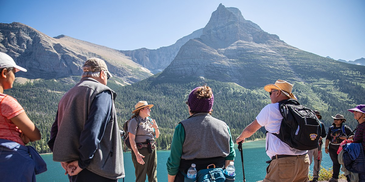 Ranger and visitors stopped on a hike overlooking St. Mary Lake.