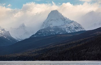 Clouds encircle snow-covered mountains by lake