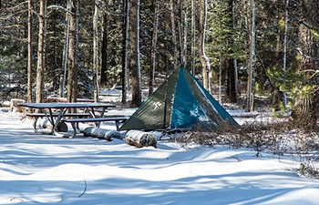 tent and picnic table in snow covered campground