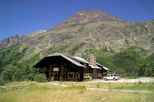 Sitting in front of a mountain is a large wood building with eave overhanging porch