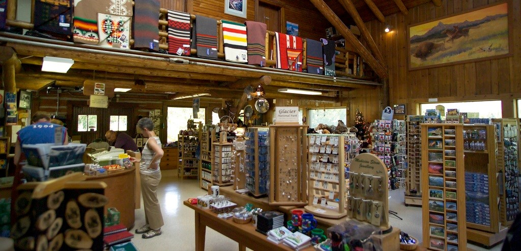 Wool blankets hang above shopper in large wooden building filled with merchandise racks