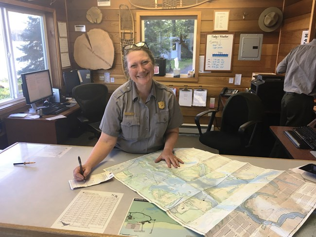Smiling park ranger attending to maps and trip planning materials at an information desk