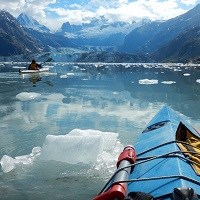 two kayakers in blue waters near a glacier and mountains