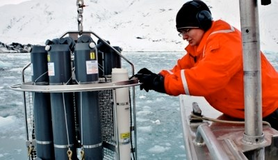 Researcher lowering scientific instruments into ocean