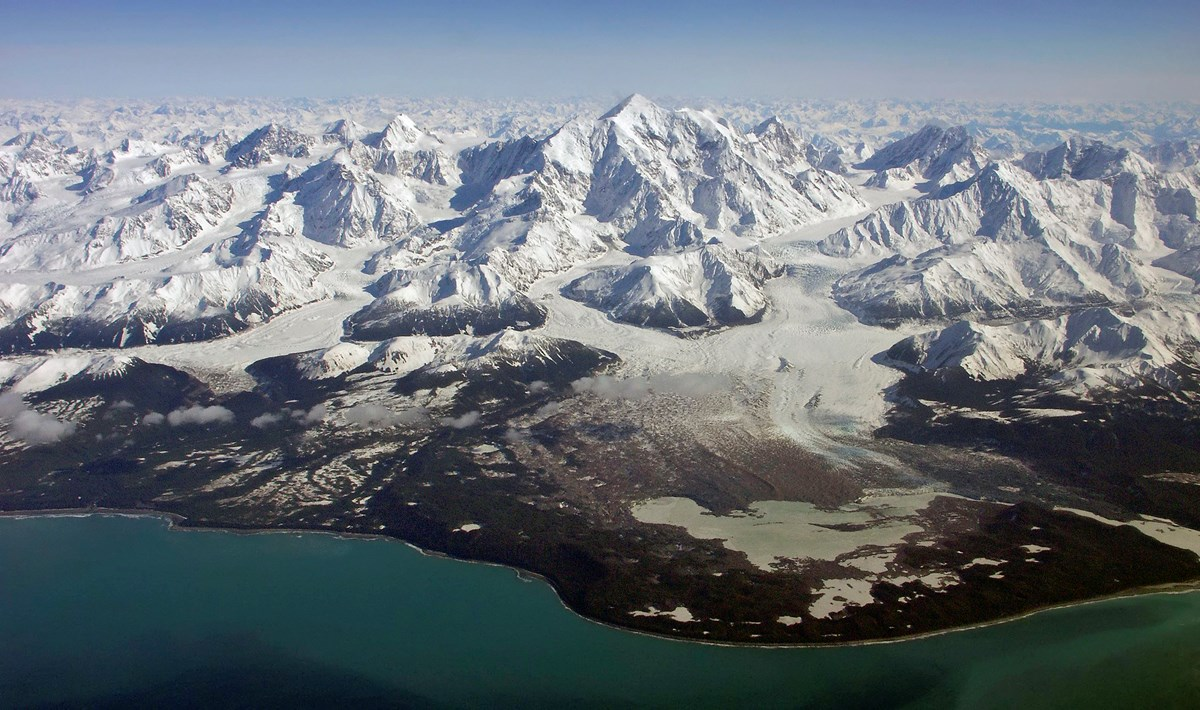 Massive snowy mountains back a coastal aerial view. A glacier flows out of the central mountain, shaping the landscape.