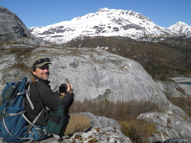A man wearing a ball cap and sunglasses points his camera towards a rocky snow-covered mountain. He smiles at the camera.
