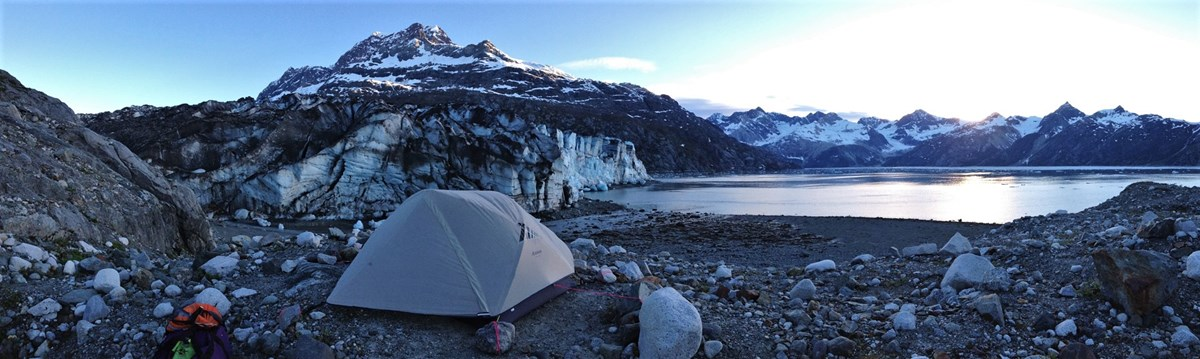 a tent near a tidewater glacier and mountains