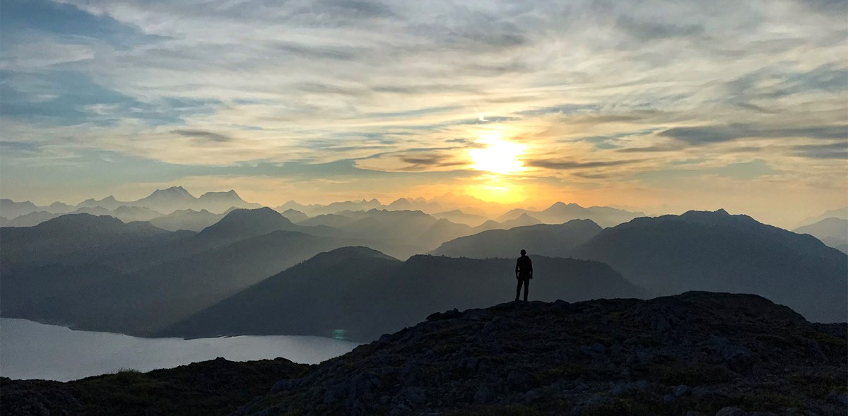Person looks toward setting sun which casts shadows on countless mountains