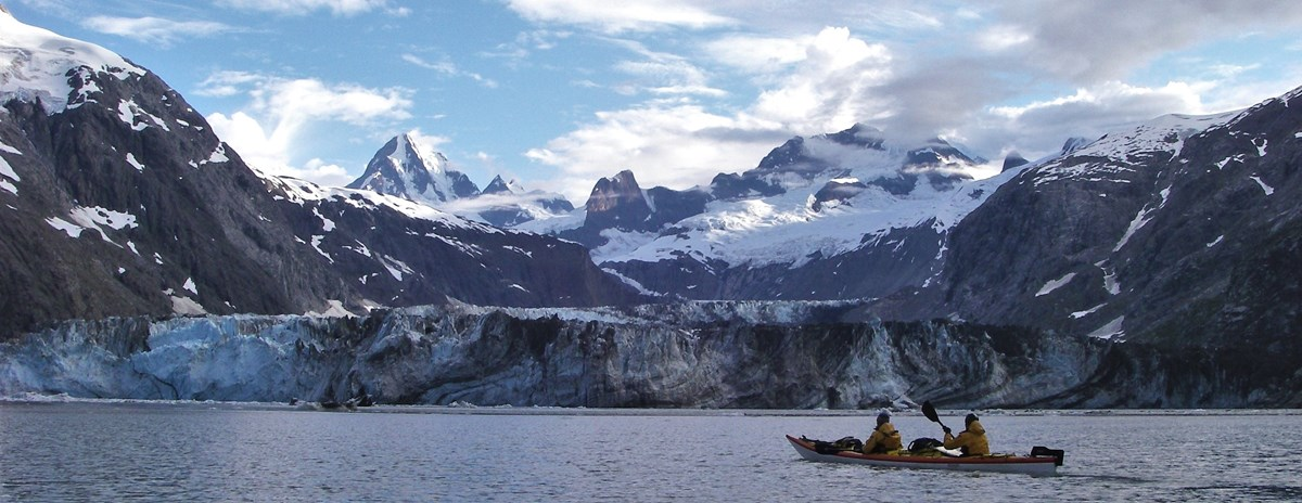 541fb0ec8 a person in a sea kayak on the water in front of a glacier and mountains