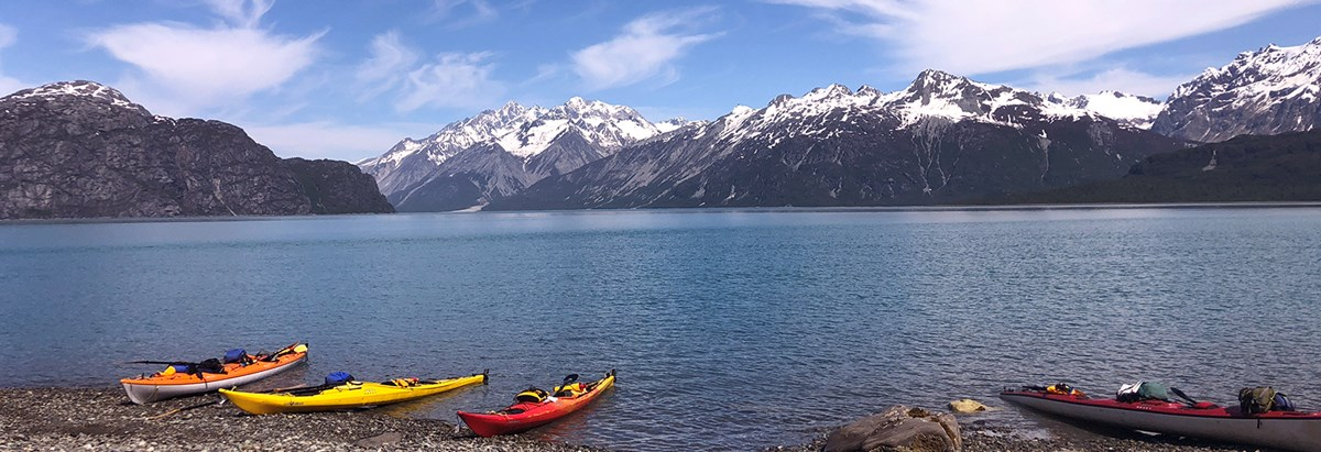 four kayaks sit on a beach in the west arm of Glacier Bay, with water and mountains in the background