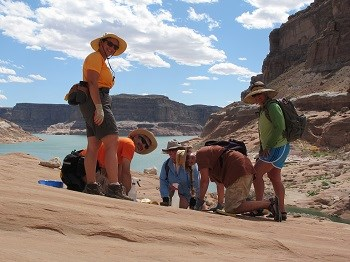 Group of people in desert hiking gear clean sloping slick rock with Lake Powell in background