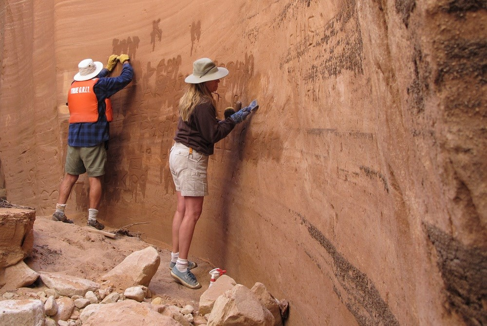 A man wearing a life jacket and a woman scrub a sandstone wall