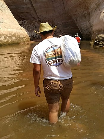 Man in GRIT tshirt heaves bag over shoulder as he walks through shallow water