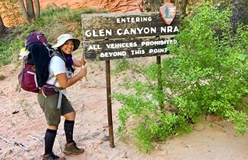 Young backpacker gives a thumbs up at wooden routered Glen Canyon entrance sign