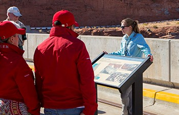 Tour guide stands behind interpretive sign while speaking to group atop dam