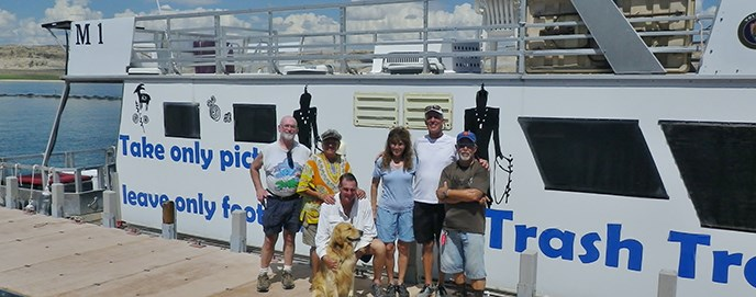 Small group of people and a dog standing in front of a white houseboat. Big blue words identify the boat as Trash Tracker.
