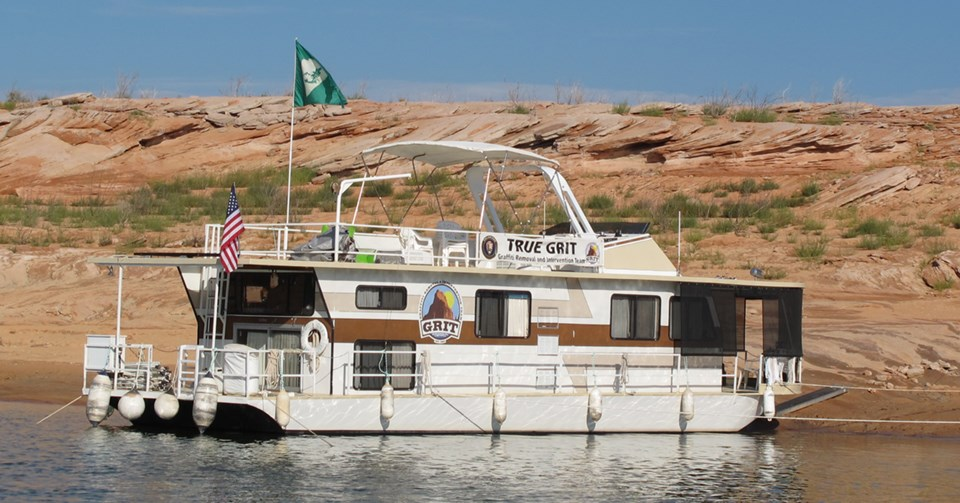 "Houseboat labeled ""True GRIT"" beached on a lake"