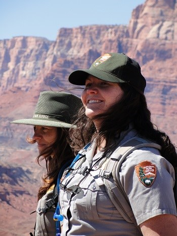 Two uniformed park rangers stand with red cliffs in distance. Their hair blows in the wind.