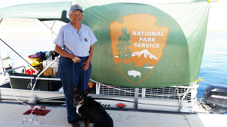 A woman and dog stand on a dock in front of a boat. boat has NPS flag.