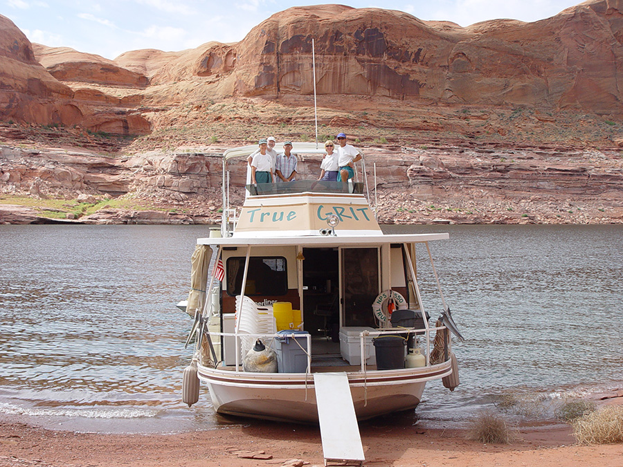 "Houseboat ""True GRIT"" beached in front of a cliff. Five people pose on the top deck."