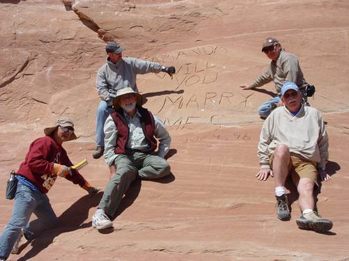 Five men sit on sandstone around a carved-in graffiti reading Amanda Will You Marry Me. They have the tools to remove the inscription.
